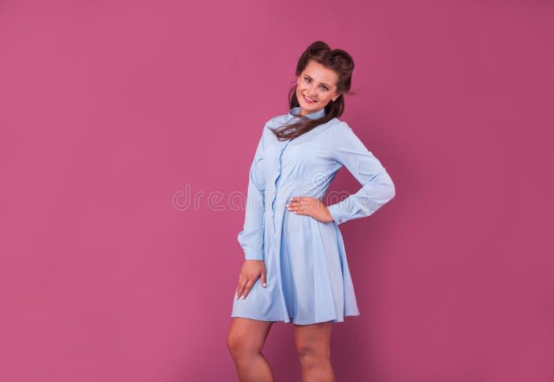 Mujer Hermosa En Un Vestido Azul En Fondo Rosado En Estudio Foto de ...
