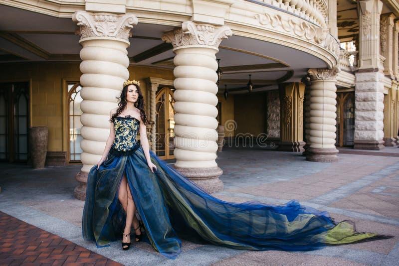 Mujer hermosa en un vestido azul lujoso con un tren largo foto de archivo libre de regalías