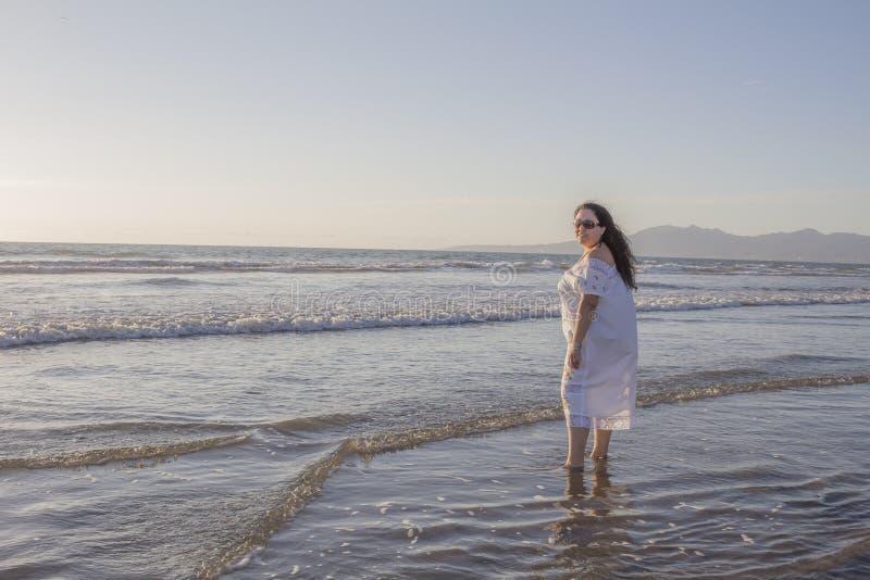 Mujer hermosa en un vestido blanco y gafas de sol que goza de la agua de mar imágenes de archivo libres de regalías