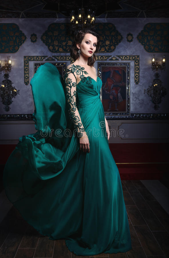 Mujer hermosa en un vestido largo verde en un fondo de rico fotografía de archivo