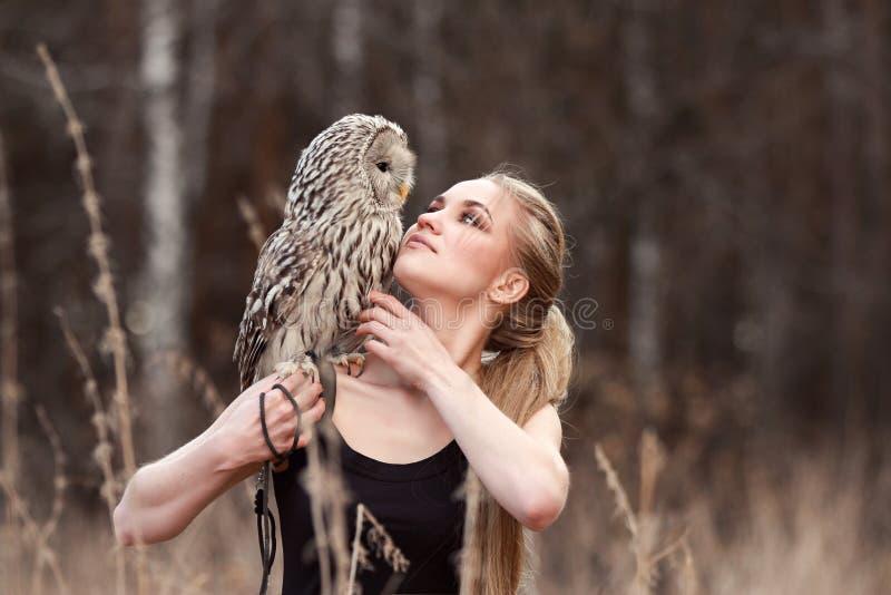 Mujer hermosa en un vestido negro con un búho en su brazo Blonde con el pelo largo en la naturaleza que sostiene un búho Muchacha imagen de archivo
