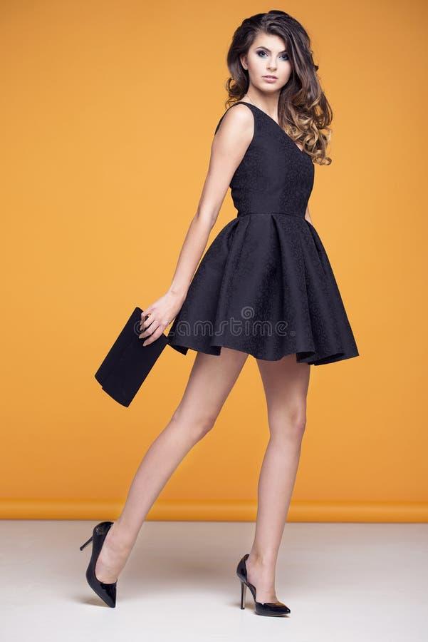 Mujer hermosa en un vestido negro elegante foto de archivo
