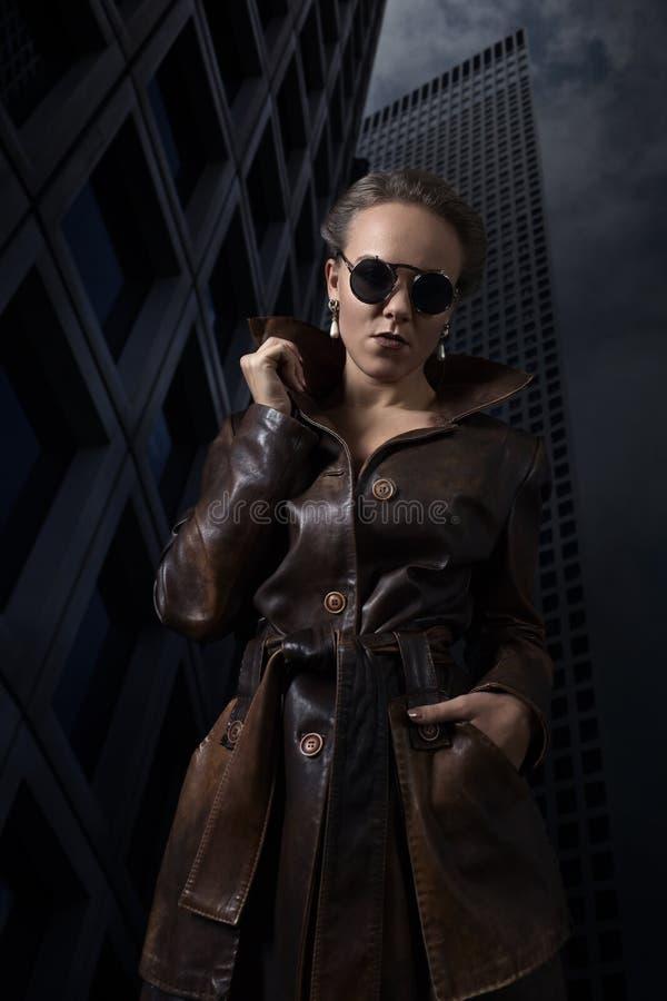 Mujer hermosa en una capa de cuero marrón antes del rascacielos imágenes de archivo libres de regalías