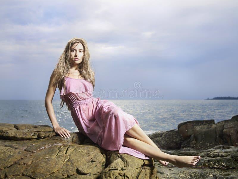 Mujer hermosa en una costa rocosa fotografía de archivo