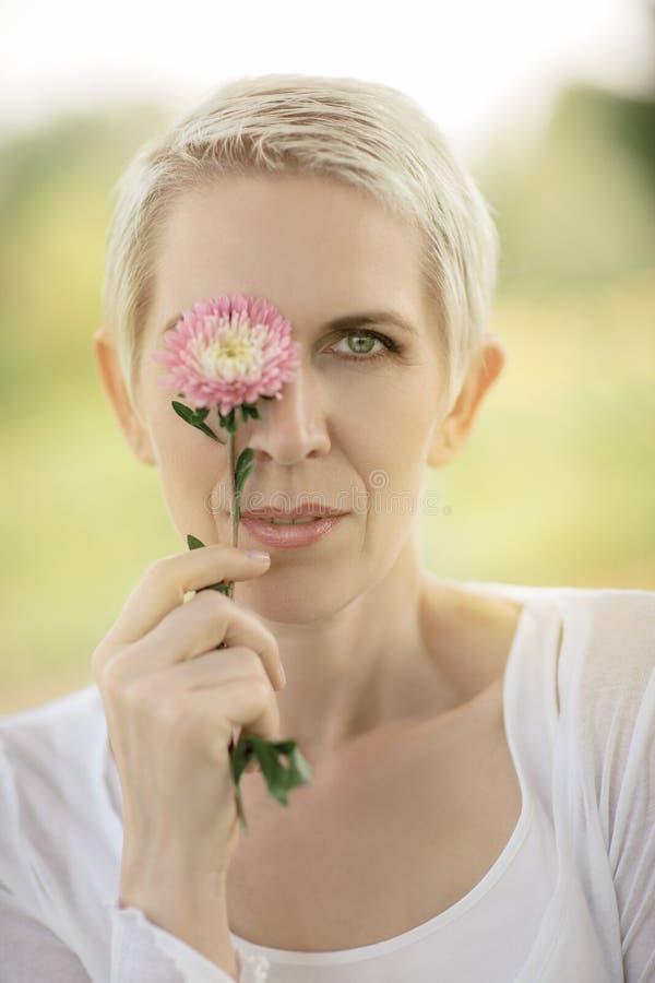Mujer hermosa en una escena rural del campo al aire libre, con las flores imagenes de archivo