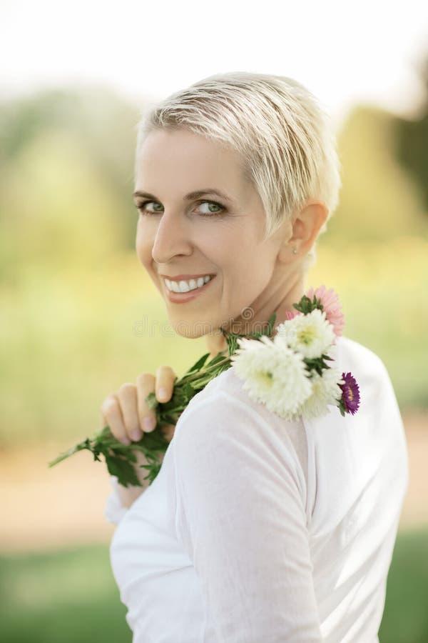 Mujer hermosa en una escena rural del campo al aire libre, con las flores imágenes de archivo libres de regalías