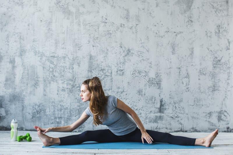Mujer hermosa en una estera de la yoga que hace estirando ejercicios dentro imágenes de archivo libres de regalías