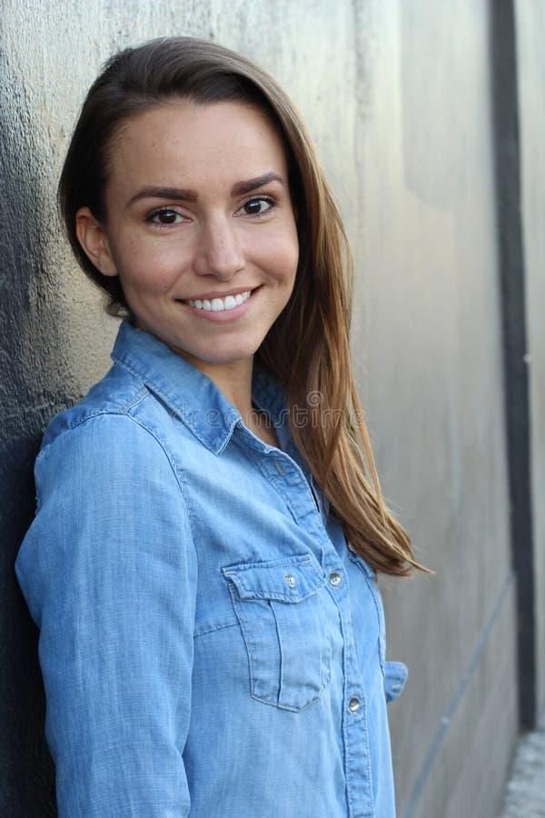 Mujer hermosa en una sonrisa casual azul de la camisa del dril de algodón foto de archivo