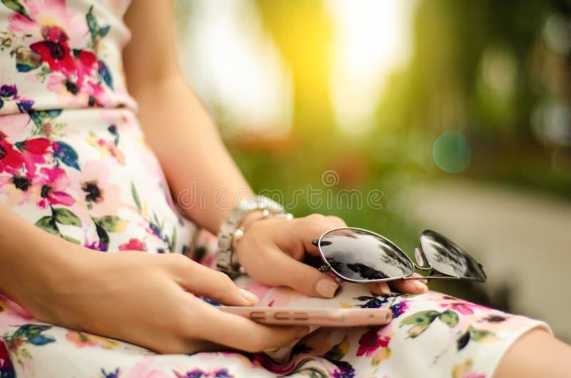 Mujer hermosa en vestido con las gafas de sol y smartphone del teléfono móvil en verano de las manos imágenes de archivo libres de regalías