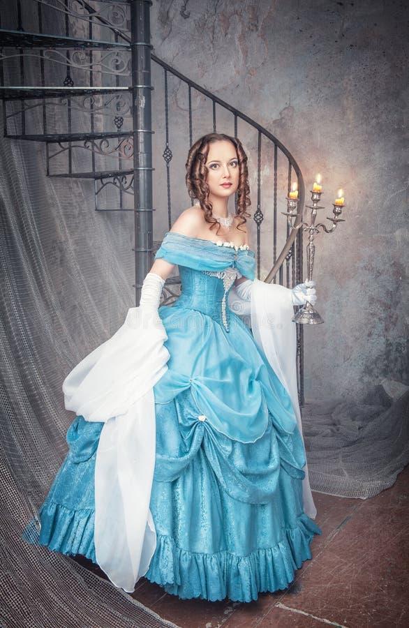 Mujer hermosa en vestido medieval azul con el candelabro imágenes de archivo libres de regalías