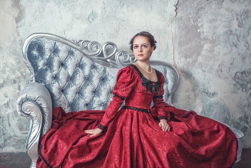 Mujer hermosa en vestido medieval en el sofá fotos de archivo libres de regalías