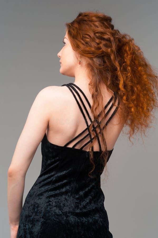 Mujer hermosa en vestido negro con los pelos rojos largos imagen de archivo