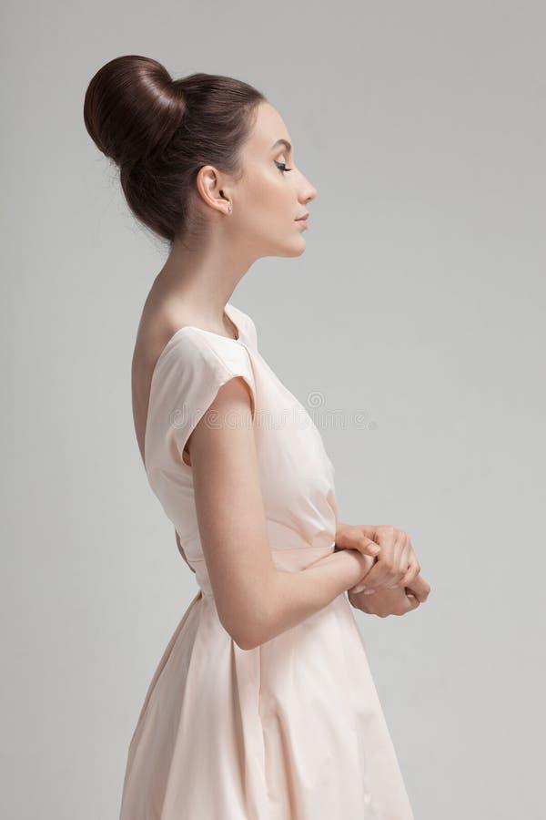 Mujer hermosa en vestido retro rosado Fondo gris foto de archivo