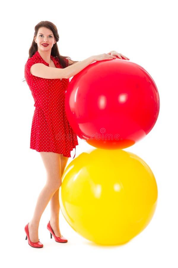 Mujer hermosa en vestido rojo con dos globos rojos y amarillos grandes foto de archivo libre de regalías