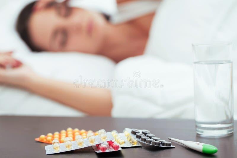 Mujer hermosa enferma que descansa en cama en casa imagenes de archivo