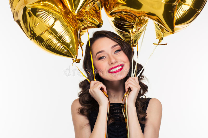 Mujer hermosa feliz alegre en el estilo retro que sostiene los globos de oro imágenes de archivo libres de regalías