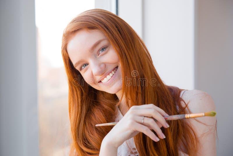 Mujer hermosa feliz alegre que coloca la ventana cercana y que sostiene la brocha imagen de archivo libre de regalías