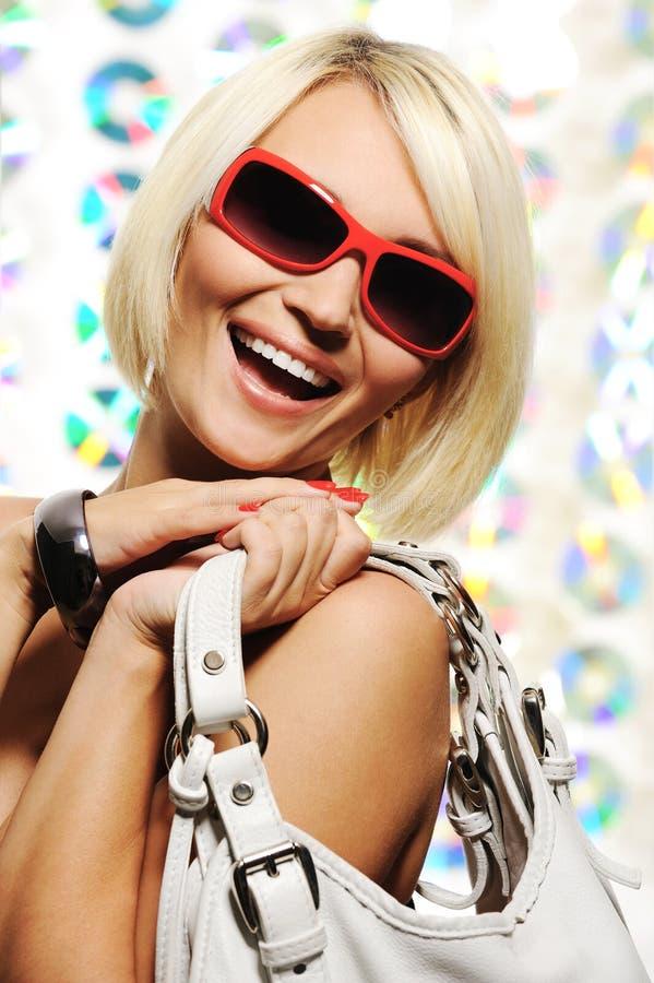 Mujer hermosa feliz con las gafas de sol rojas fotos de archivo libres de regalías