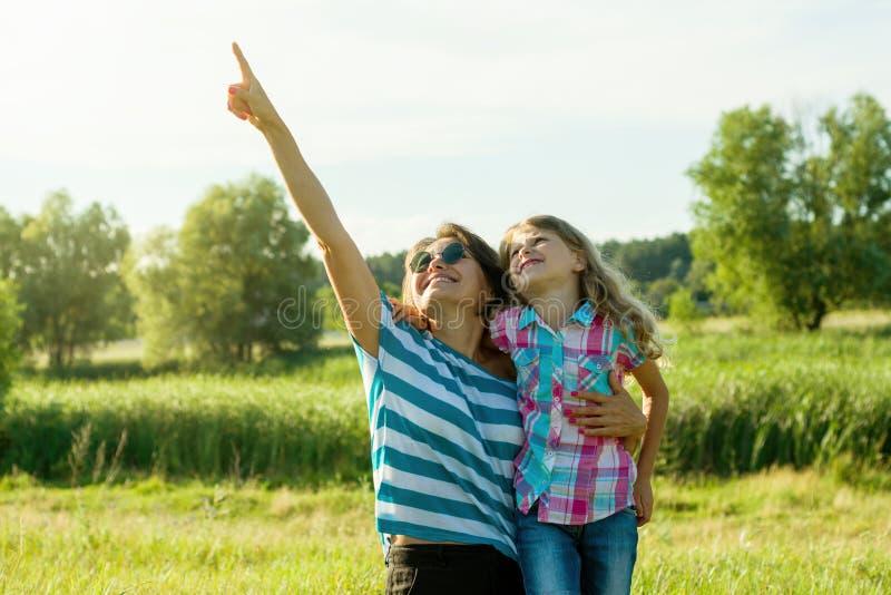 Mujer hermosa feliz con un niño que señala un finger en el cielo, fotos de archivo libres de regalías