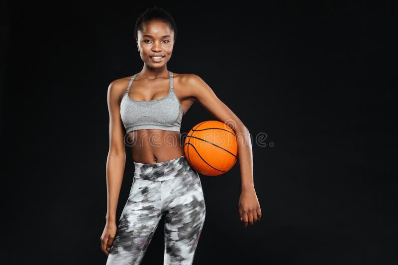 Mujer hermosa feliz de los deportes que sostiene la bola sobre fondo negro imágenes de archivo libres de regalías