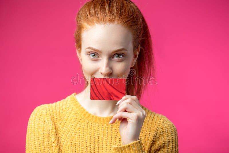 Mujer hermosa feliz del jengibre que sostiene la tarjeta de crédito aislada en fondo rosado foto de archivo libre de regalías