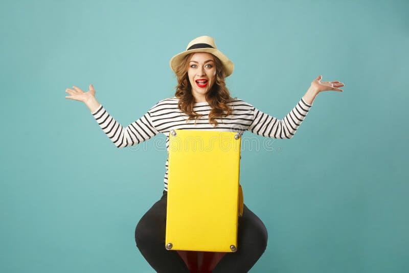 Mujer hermosa feliz joven en el sombrero del verano que sostiene suitcas amarillos fotos de archivo