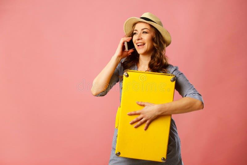 Mujer hermosa feliz joven en el sombrero que lleva a cabo la maleta amarilla y t imagen de archivo libre de regalías