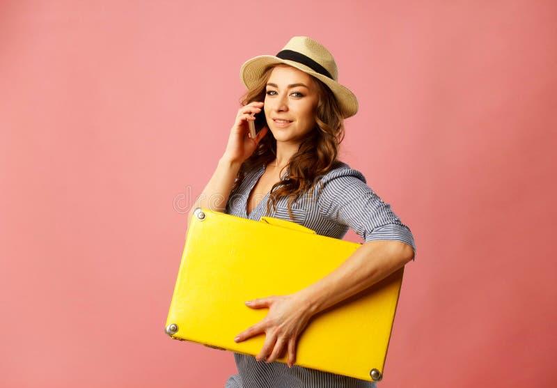 Mujer hermosa feliz joven en el sombrero que lleva a cabo la maleta amarilla y t foto de archivo