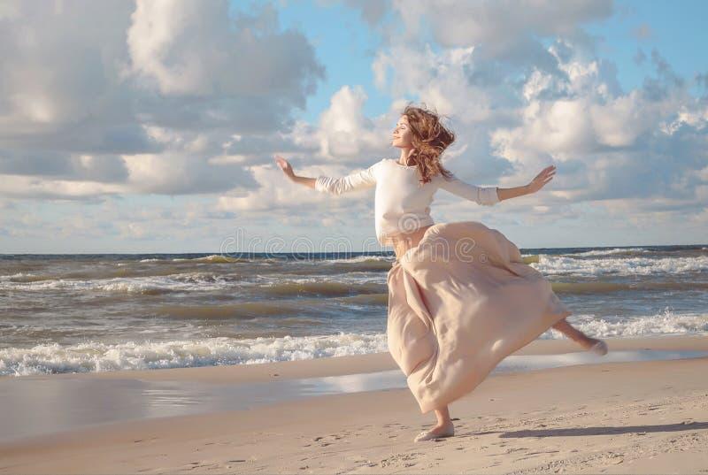 Mujer hermosa feliz joven que salta en una playa en verano Imagen de una mujer que salta sobre el océano en la puesta del sol, si imagenes de archivo