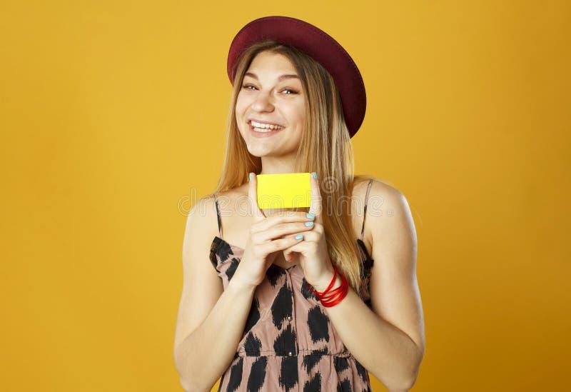 Mujer hermosa feliz joven que sostiene la tarjeta de crédito vacía en las manos o imagen de archivo