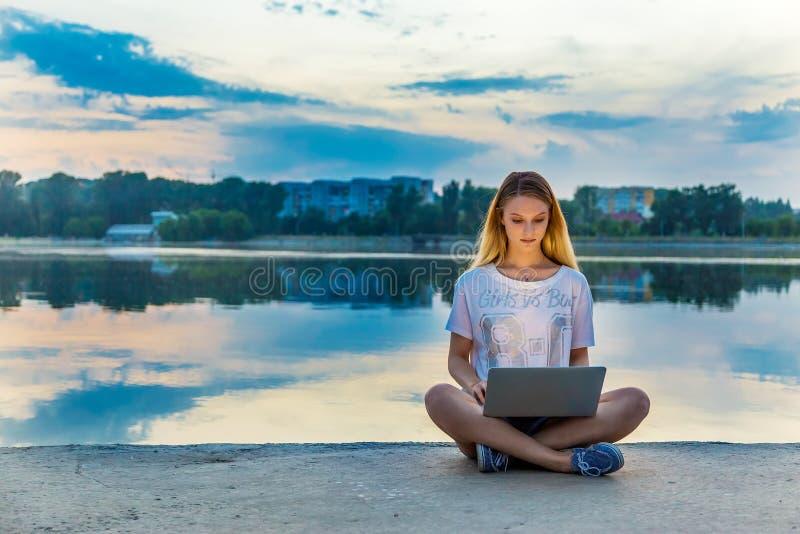 Mujer hermosa feliz, muchacha con el ordenador portátil que practica surf el web cerca por el lago imagen de archivo