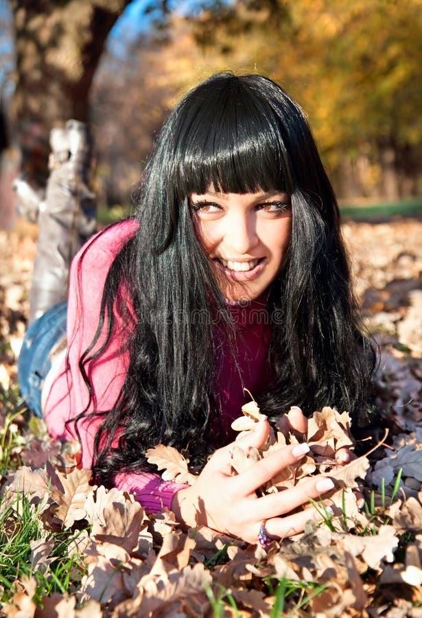 Mujer hermosa feliz que miente en el parque del otoño foto de archivo