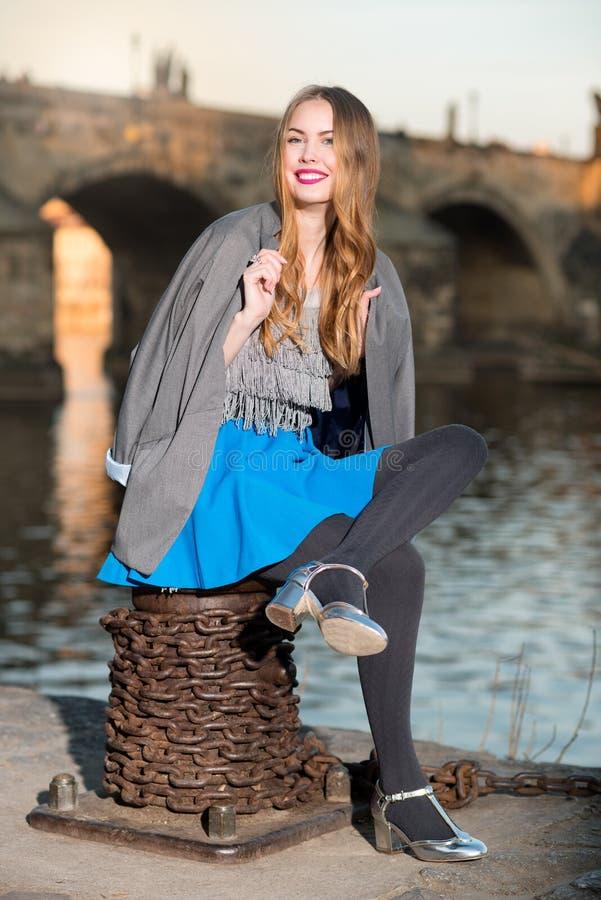 Mujer hermosa feliz que se sienta cerca del río en la ciudad fotografía de archivo