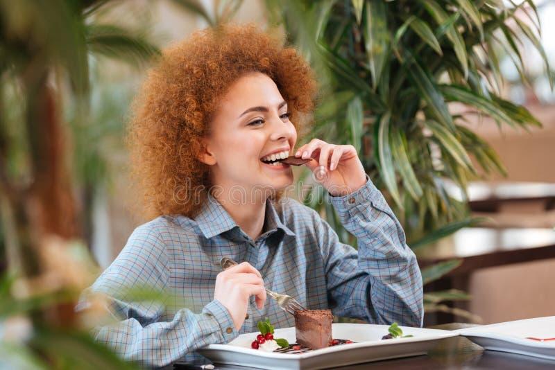 Mujer hermosa feliz que se sienta en café y que come el postre del chocolate imagenes de archivo