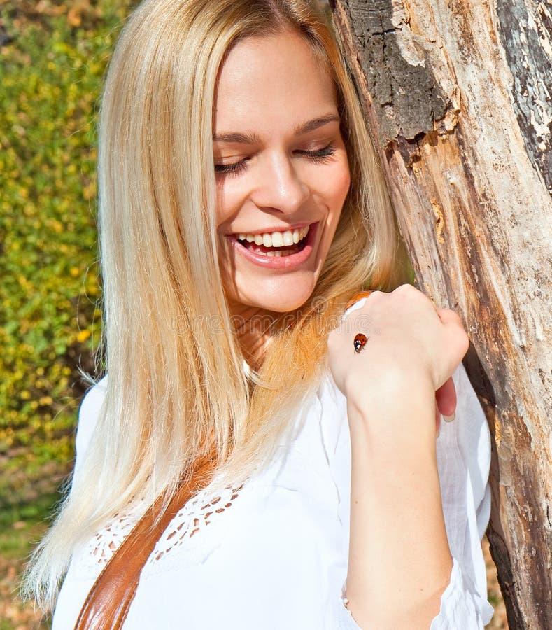 Mujer hermosa feliz que sostiene suavemente un ladybug imágenes de archivo libres de regalías