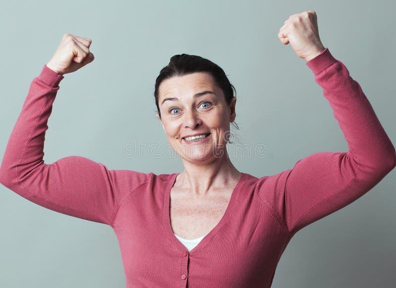 Mujer hermosa feliz 40s que dobla sus músculos para arriba imagen de archivo