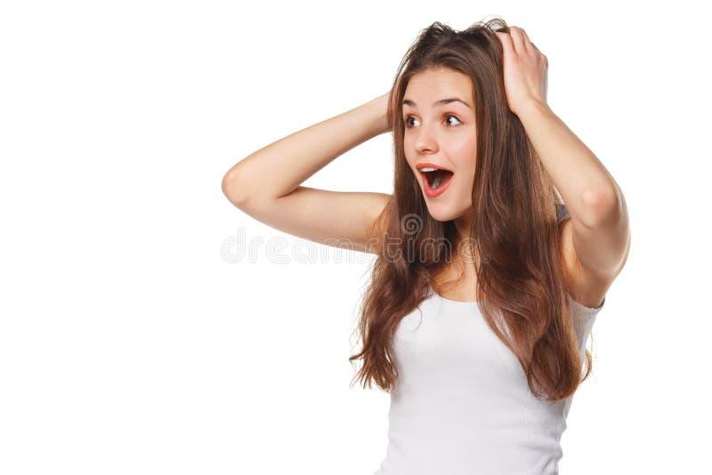 Mujer hermosa feliz sorprendida que mira de lado en el entusiasmo Aislado en el fondo blanco imagen de archivo