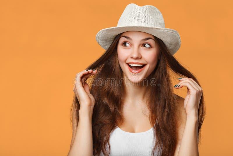 Mujer hermosa feliz sorprendida que mira de lado en el entusiasmo, aislado en fondo anaranjado imagenes de archivo