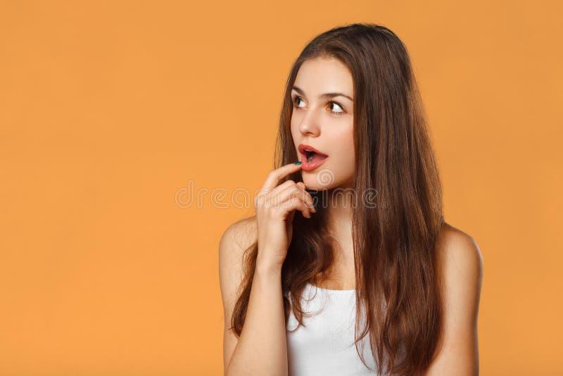 Mujer hermosa feliz sorprendida que mira de lado en el entusiasmo En fondo anaranjado imágenes de archivo libres de regalías