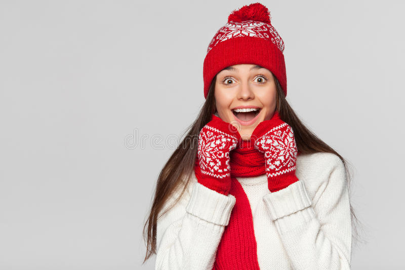 Mujer hermosa feliz sorprendida que mira de lado en el entusiasmo Muchacha de la Navidad que lleva el sombrero hecho punto y las  fotos de archivo