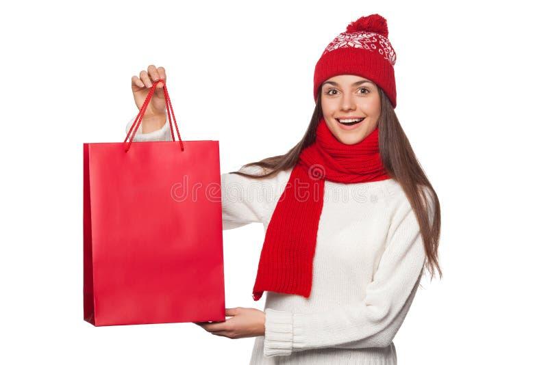 Mujer hermosa feliz sorprendida que sostiene el bolso rojo en el entusiasmo, haciendo compras Muchacha de la Navidad en venta del fotografía de archivo libre de regalías