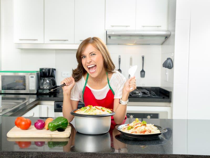 Mujer hermosa hispánica que cocina en cocina moderna imágenes de archivo libres de regalías