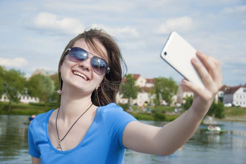 Mujer hermosa, instagram mujer que toma un selfie con el teléfono elegante al aire libre en la ciudad en día de verano soleado Ti imágenes de archivo libres de regalías