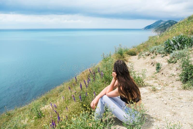 Mujer hermosa joven 25-30 años que se sientan en la montaña y las miradas en el mar, vista lateral fotos de archivo