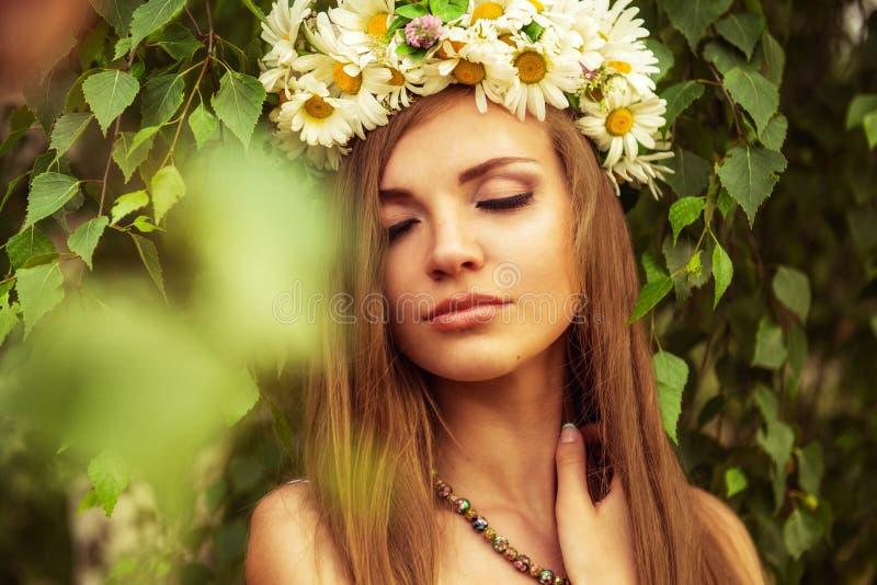 Mujer hermosa joven al aire libre en un wreth que lleva del birchwood de la margarita foto de archivo