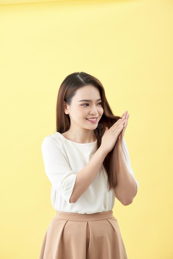 Mujer hermosa joven asiática que sonríe y que toca lisa su pelo, maquillaje natural, cara de la belleza, aislada sobre fondo azul foto de archivo