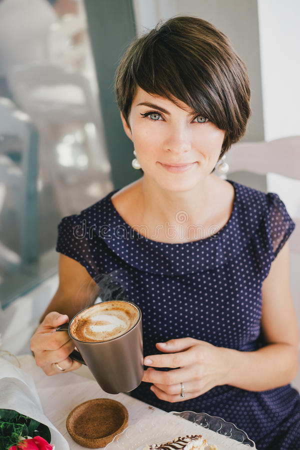 Mujer hermosa joven con el pelo corto que bebe cociendo el café al vapor foto de archivo