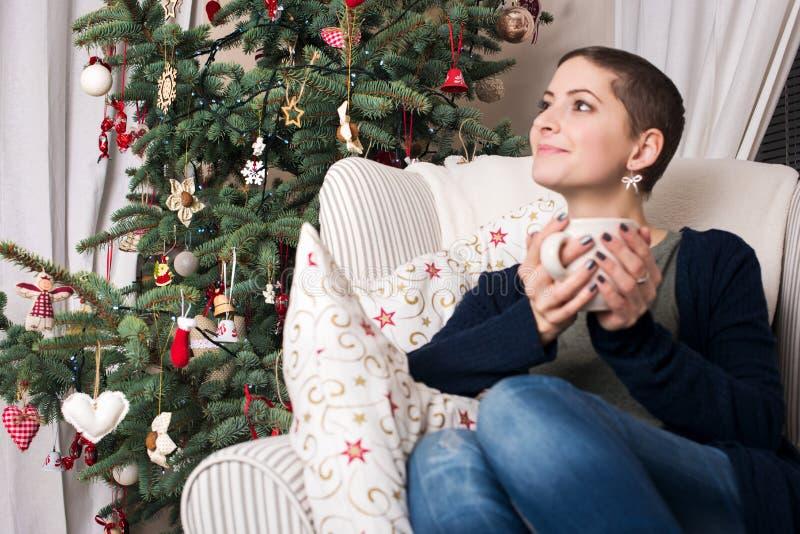 Mujer hermosa joven con el pelo corto que goza de la taza de té, sentándose delante del árbol de navidad imagenes de archivo
