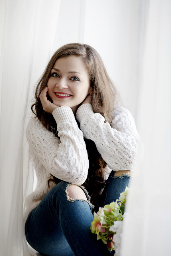 Mujer hermosa joven con el pelo largo en el suéter y los tejanos que se sientan cerca de la ventana foto de archivo libre de regalías