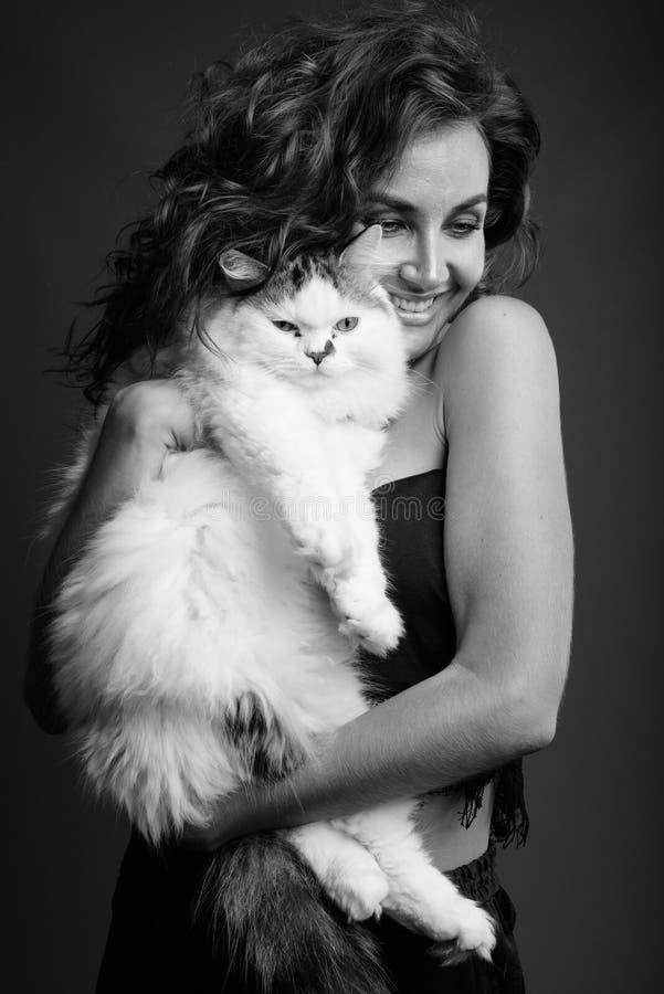 Mujer hermosa joven con el pelo rizado que presenta en blanco y negro imagenes de archivo